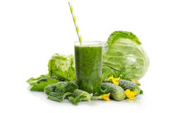Glass with green smoothie and vegetables, leaves, flowers. On white background Stock Images