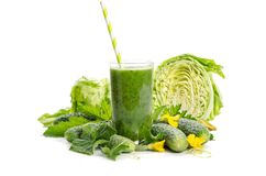 Glass with green smoothie  and  vegetables, leaves, flowers. On white background Stock Photos