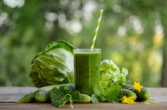 Glass with green smoothie on a wooden table and  vegetables Stock Photos