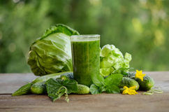 Glass with green smoothie on a wooden table and vegetables Royalty Free Stock Photography