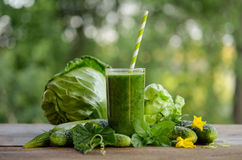 Glass with green smoothie on a wooden table and vegetables Stock Photography