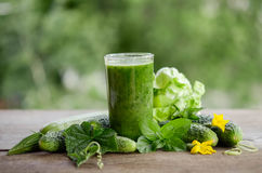 Glass with green smoothie on a wooden table and vegetables Stock Image
