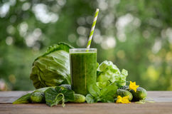 Glass with green smoothie on a wooden table and  vegetables Stock Images