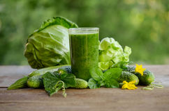 Glass with green smoothie on a wooden table and vegetables Stock Photo
