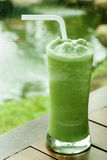 Glass of green tea frappe on wooden table in garden Stock Photography