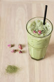 Glass of green tea latte decorated with dried rose Stock Photo