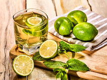 Glass with green transparent lime drink and mint napkin. Stock Image