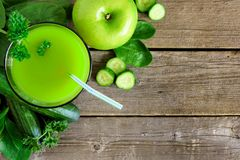 Glass of green vegetable juice, downward view on rustic wood. Glass of fresh green vegetable juice, downward scene over a rustic wood background stock image