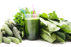 Glass of green vegetable juice. And green vegetables on the background Stock Photos