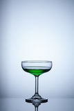 Glass of green water on blue background. Object Royalty Free Stock Photography