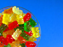 Glass of gummy bears. Against blue background Royalty Free Stock Photography
