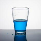 Glass half full of blue liquid. On light background Stock Photo