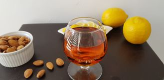 Glass half full with brandy on brown table royalty free stock images