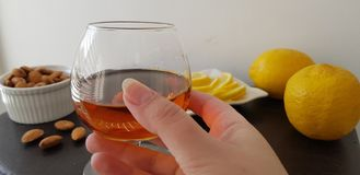 glass half full with brandy over brown table with almonds and lemons stock photo