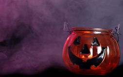 Glass halloween pumpkin candle holder with smoke Royalty Free Stock Photos