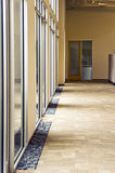 Glass Hallway. A office building hallway next to some large glass windows Stock Photo