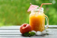 Glass with a handle. With peach juice red tubule and red umbrella stock image