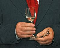 Glass in hands. Glass of white wine in hands of speaking manager royalty free stock image