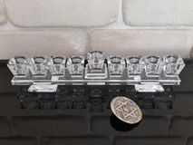A glass Hannuka and silver dreidel on a black piano with stone wall in the background. Picture taken in my house for Hannuka Jewish holiday stock photography