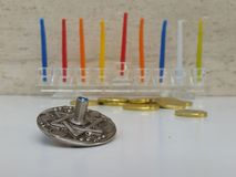 A glass Hannukiah filled with colourful candles on a white table with some scattered chocholate coins and a silver dreidel. Picture taken in my house for Hannuka Royalty Free Stock Photography