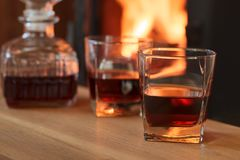 Glass of hard liquor in front of the fireplace. Glass of hard liquor in front of the fireplace at night Royalty Free Stock Images
