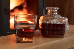 Glass of hard liquor in front of the fireplace. Glass of hard liquor in front of the fireplace at night Stock Image