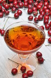 Glass of  hawthorn liqueur and hawthorn fruit Royalty Free Stock Images