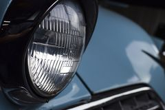 GLASS HEADLIGHT OF VINTAGE BLUE CAR. A shiny, gleaming glass headlight peeks out from a vintage 1950s blue car stock photos
