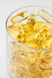 Glass of health with fish oil capsules Royalty Free Stock Image
