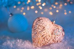 Glass heart and ball on a snow and toned blurred blue background of glittering bokeh with lights. Christmas decoration. Copy space royalty free stock photos
