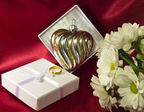 Glass heart in a box with flowers and a golden ring Stock Image