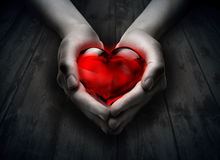Glass heart in the heart hand. Wood background royalty free stock photos