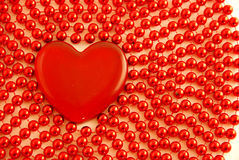 Glass Heart and red beads. Red Glass Heart among red beads Royalty Free Stock Photos