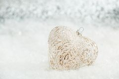 Glass heart on a snow. Blurred white background of glittering bokeh with glowing lights. Christmas decoration. Copy space stock images