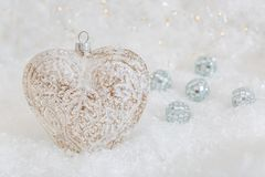 Glass heart on a snow. Blurred white background of glittering bokeh with glowing lights. Christmas decoration. Mirror balls. Christmas decoration renaissance royalty free stock images