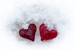 Glass hearts in melting snow Royalty Free Stock Image