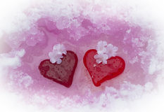 Glass hearts in melting snow Royalty Free Stock Images