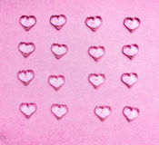 Glass hearts on pink background Stock Photos