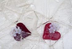 Glass hjärtor i bruten is arkivfoto
