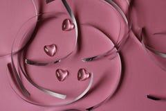 Glass hjärtor och rosa bakgrund Arkivfoton