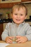 glass holding för pojkedrink Royaltyfri Bild