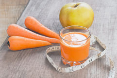 Glass of homemade juice, apple and carrot on wooden board Stock Photography