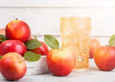 Glass of homemade organic apple cider with fresh apples in box on wooden background with sun light Stock Photos