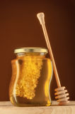 Glass of honey with honeycomb Stock Image