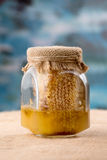 Glass honey jar with bee pollen, honeycombs. Close-up sacking and blue background royalty free stock photography