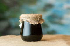 Glass honey jar. Covered with burlap close-up sacking and blue background stock photos