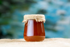 Glass honey jar. Covered with burlap close-up sacking and blue background royalty free stock image