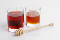 Glass and honey stick. Glass on the table with honey stick Royalty Free Stock Images