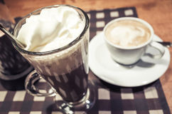 Glass of hot chocolate and cup of cappuccino coffee Royalty Free Stock Image