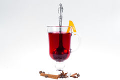 Glass of hot mulled wine with apples and oranges, cloves and vanilla sticks on a white background. Hot Christmas drink. Stock Image